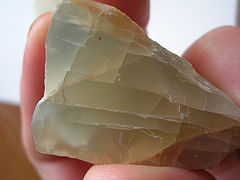 A chunk of grayish yellow moonstone which shows fracture lines and a blue glow in some portions.