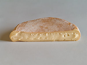 Half-circle of soft tan cheese, cut side forward, on white table