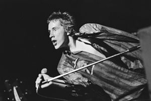 Black-and-white photo of a spiky-haired youth singing into a microphone