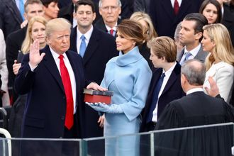 With right hand raised, Donald Trump looks at John Roberts with his back to the camera, as Melania Trump and others watch.
