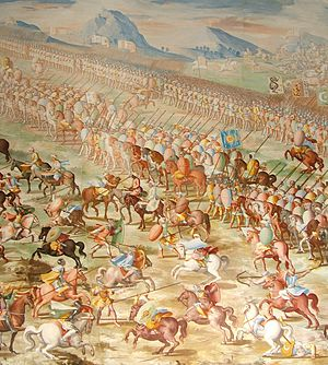 A painting of a battle with a long line of mounted riders side-by-side in front of a line of marching men. In front of the riders are a number of individual horsemen fighting.