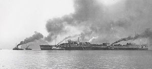 Small tugboats surround a partially completed large ship; dark smoke is rising from the boats
