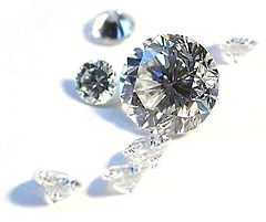 Several white diamonds with brilliant cuts lie scattered across a white background.