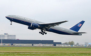 Boeing 7777 airliner taking off. The jet's nose is angled upwards as it lifts above the runway, with landing gear still deployed.