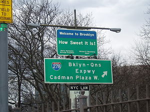 "Rectangular blue-and-green sign reading, ""Welcome to Brooklyn. How sweet it is!"""