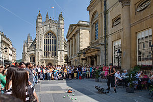 Gray paved area with lots of people around brightly dressed performer. To the right is a yellow stone building and in the background the tower of the abbey.