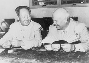 A balding Russian man (Nikita Kruschev) and a younger Chinese man (Mao Zedong) sit and smile, the balding man holding a fan