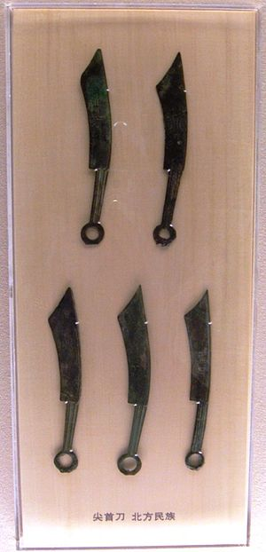 Five elongated bronze knives, corroded over time with a green color, with a ring handle on the end opposite the blade