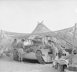 Three men work on a tank, which is under a net and facing to the left.