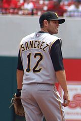 "A man wearing a gray baseball uniform with the name ""Sanchez"" and the number ""12"" on the back, a black cap bearing, and a baseball glove stands on a baseball field"