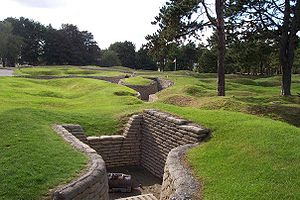Curved trench lines, preserved in concrete are surrounded by shell craters that are now covered in grass. In the immediate foreground, a small half-destroyer piece of artillery sits in a three walled position that is off of the main trench line.