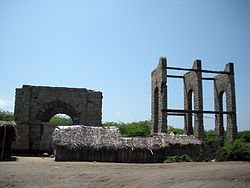 Photograph of the ruined Dhanushkodi Railway Station, surrounded by weeds
