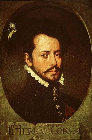 "Old painting of a bearded young man facing slightly to the right. He is wearing a dark jacket with a high collar topped by a white ruff, with ornate buttons down the front. The painting is dark and set in an oval with the letters ""HERNAN CORTES"" in a rectangle underneath."