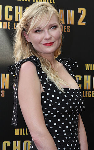 Kirsten Dunst is pictured with wavy blonde hair and wearing a black dress with white polka dots, with the straps tied in bows.