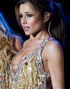 With her brown hair tied back, a female wearing a glittery outfit is performing with a headset microphone.