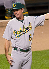 "A man wearing a gray baseball uniform with ""Oakland"" and the number ""6"" written across the chest in green letters and a green cap with a yellow ""A"" on it stands on a baseball field"