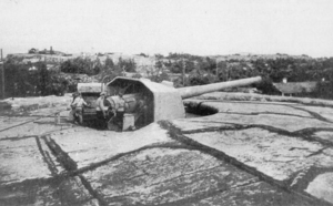 A large gun with a crew of three stands on rocky ground in summer.