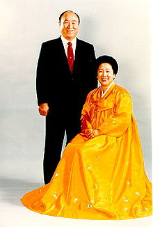 Moon (standing in suit) and his wife (seated in long yellow dress)