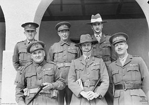 Six officers pose for a formal group portrait. Two are wearing slouch hats, the remainder are wearing peaked caps. All have multiple ribbons.