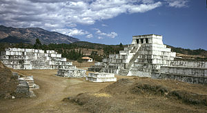 A cluster of squat white step pyramids, the tallest of them topped by a shrine with three doorways. In the background is a low mountain ridge.