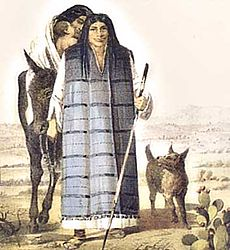 Full length portrait of a man in his thirties wearing a long robe, woman and child visible behind him and dog to his left