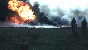 Huge oil fire, with two soldiers in foreground