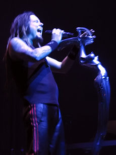 A man with his eyes closed and mouth open, holding a microphone; he is wearing dark clothing and wrist bands.