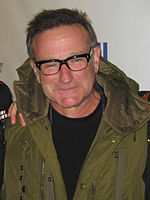 A picture of a bespectacled man wearing a green coat over a black shirt.