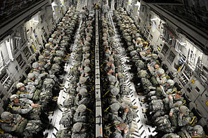 Paratroopers in four rows sit strapped in.
