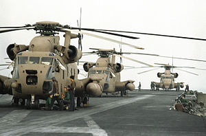 three sand painted RH-53 Sea Stallion helicopters sit on the flight deck of an aircraft carrier