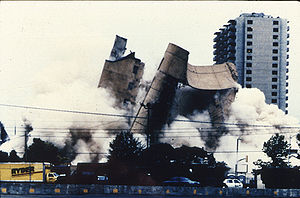 The Alfred P. Murrah building is being demolished, and the image shows the building in mid-collapse. A Ryder truck is visible at the bottom left, and the Regency Towers building can be seen in the background at the far right. The demolition has created large clouds of dust that take up a portion of the image.