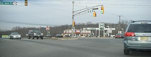 A four-way intersection at a traffic light between a divided highway and a two-lane road. A traffic light resides in the highway median, with a sign blade for U.S. Route 202 and Route 31. Another traffic light arm is to the left with a sign blade reading Old York Road Route 179. A Hess gas station is in the background