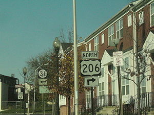 A street in an urban area with a sign reading north U.S. Route 206 right in the foreground and a Route 31 left sign in the background