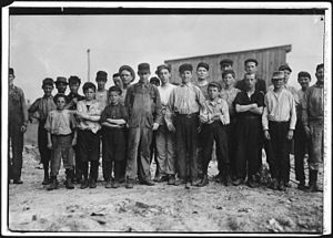 20-25 males facing camera in a row, mostly children. Ages vary. They are in work clothes. Some are dirty. Some wear caps. They stand on dirt with a wooden building behind them.