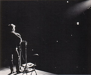A spotlight shines on Dylan as he performs onstage.