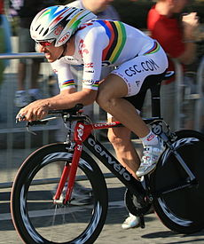 A cyclist wearing a rainbow skinsuit while riding a bike.