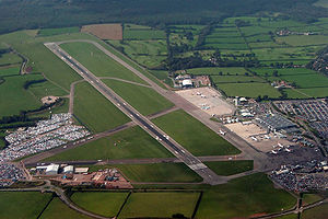 An aerial view of an airport with one main runway, car parks on the left and right, and aircraft parked outside terminal buildings on the right.