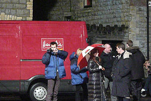 "Tennant, Piper, Tate, and Barrowman stand in front of a van that carries the branding of a fictional company in Doctor Who, which is parked outside a church. Tennant is holding a video camera and is filming the ""David Tennant's Video Dairies"" featurette for the series DVD and Tate is holding an open umbrella coloured in the Welsh national colours."