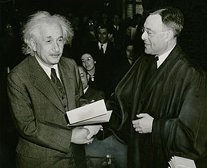 photograph of a white haired man on left (Albert Einstein) shaking hands with a man in a black robe.