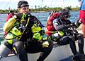Two scuba divers in one-piece wetsuits and full scuba gear sitting in a boat, preparing to dive. Both divers are wearing tech rigs with back inflation BC and sling cylinders for decompression gas