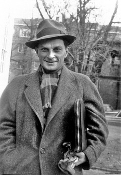 A smiling man in a hat and heavy winter coat and scarf, carrying a portfolio tucked under his arm