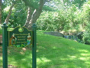 "photograph of a multi-coloured carved wooden sign which reads ""Anne Hutchinson/Mary Dyer Memorial Herb Garden,"" behind which is a scenic small waterfall surrounded by green foliage."