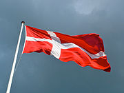 In the sky flies a red flag with a white cross whose vertical bar is shifted toward the flagpole.