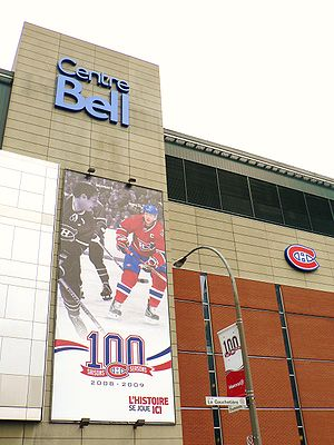 "Façade of the Bell Centre. On the wall is a banner celebrating the Canadiens centennial, featuring two players, one in black and white and one in color, and the Canadiens logo in front of a ""100""."