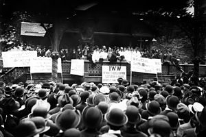 Black and white photograph of a speaker rallying a large crowd. In front of the stage, facing the audience, are several signs, in various languages, displaying demands.