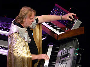 Rick Wakeman, surrounded by several keyboard instruments and wearing his customary robe, plays a keyboard with one hand and programs a Minimoog synthesizer with the other