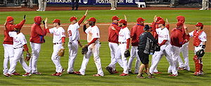 A group of men in white baseball uniforms with red pinstripes and red baseball caps high-five each other while passing in lines moving in opposite directions.
