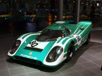 A picture of a green racing sports car from the front in an indoor setting