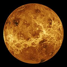 A false-colour image of Venus: ribbons of lighter colour stretch haphazardly across the surface. Plainer areas of more even colouration lie between.