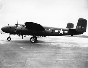 Black and white photo of an early bomber parked perpendicular to camera, facing left. Rearward of the wing is a star in front of horizontal stripes.